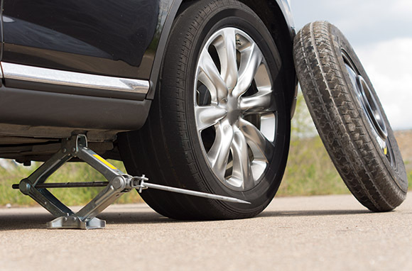 Photo: Changing a Flat Tire via Shutterstock