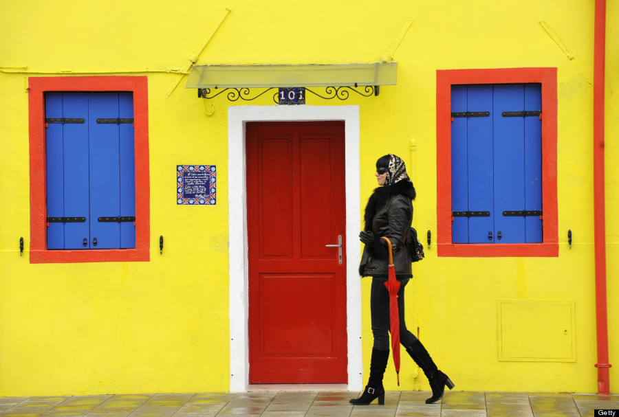Young woman walking along the street, Burano, Venice, Veneto, Italy