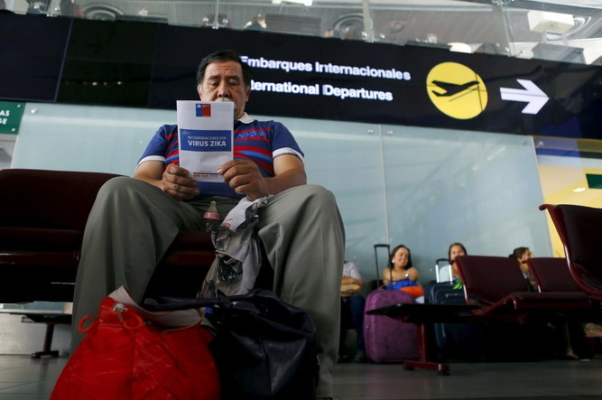 A man reads a Zika virus flyer from an information campaign by the Chilean Health Ministry at the departures area of Santiago's international airport, Chile. Ivan Alvarado/Reuters
