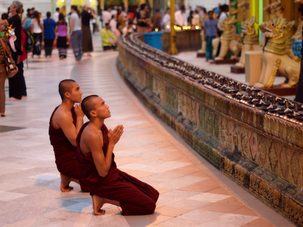 Two young monks pray in front of Shwedagon Pagoda in Yangon.