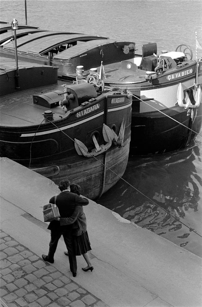 Lovers walk past barges on the Seine. Photo: Erich Hartmann / Magnum Photos