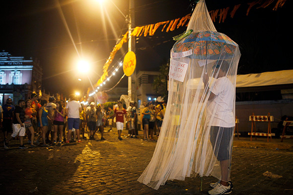 A reveler stands beneath a mosquito net, as a satirical costume, during Carnival celebrations in Olinda, sister city to Recife, which remains a hotbed of Zika virus outbreaks in Brazil. (Photograph by Mario Tama/Getty Images).