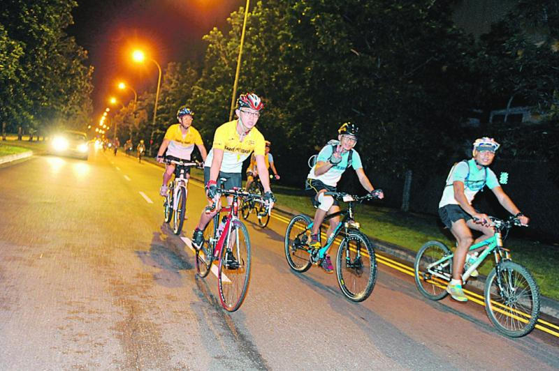 A few cyclists on their bicycles cycling at night. See a side of Singapore you rarely glimpse on night time cycle. Photo credit: Money Sense