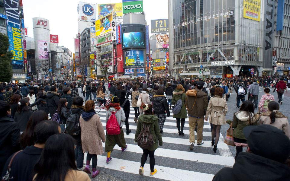 Urban bustle, people crossing a busy cross walk in Shibuya, Tokyo, Japan