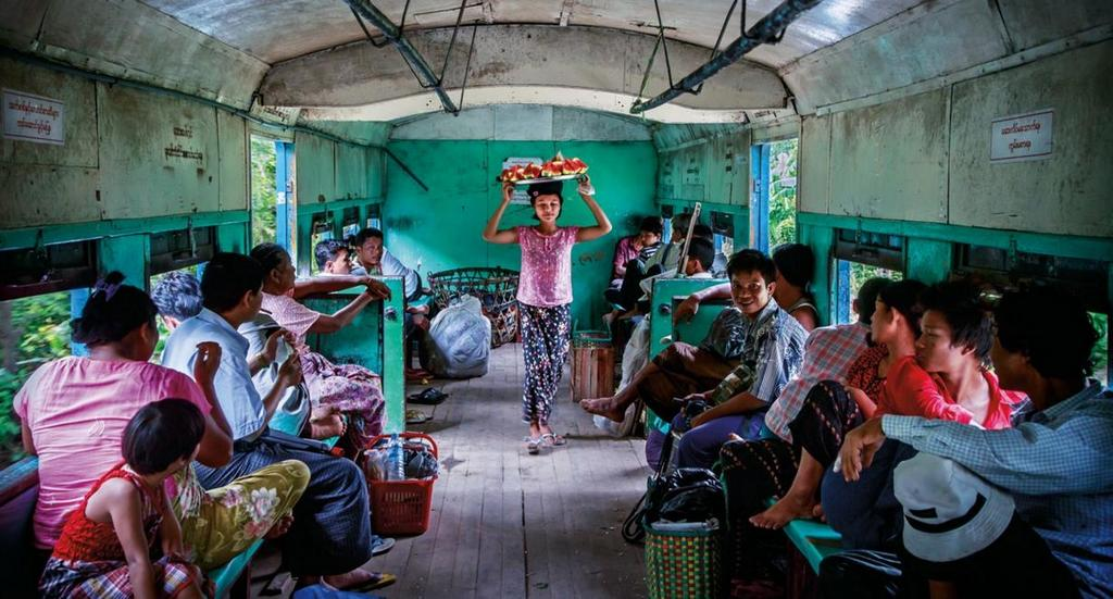 A girl selling watermelon on a moving train (built in the 1950's) that circles the entire city of Yangon