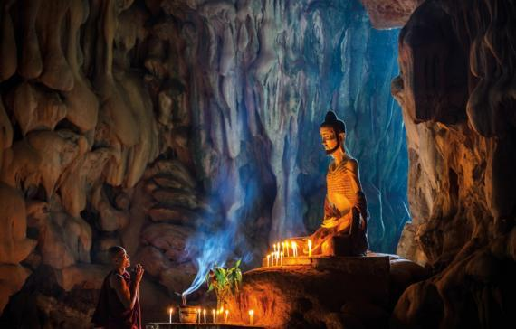 A monk praying to a figure of Prince Siddhartha during austerity stage in a 500 million year old cave