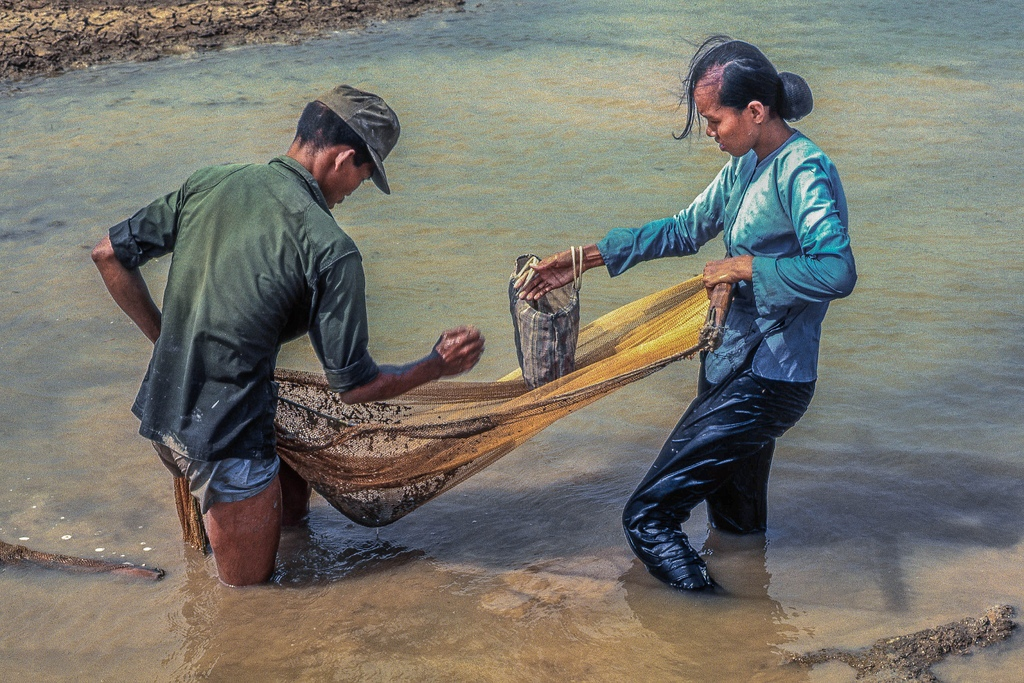 ARVN soldier and his wife gleening the last fish from the drying rain ponds by the Binh Duc air strip west of My Tho in 1969. (Dinh Tuong Province, Vietnam) (scanned colour slide)