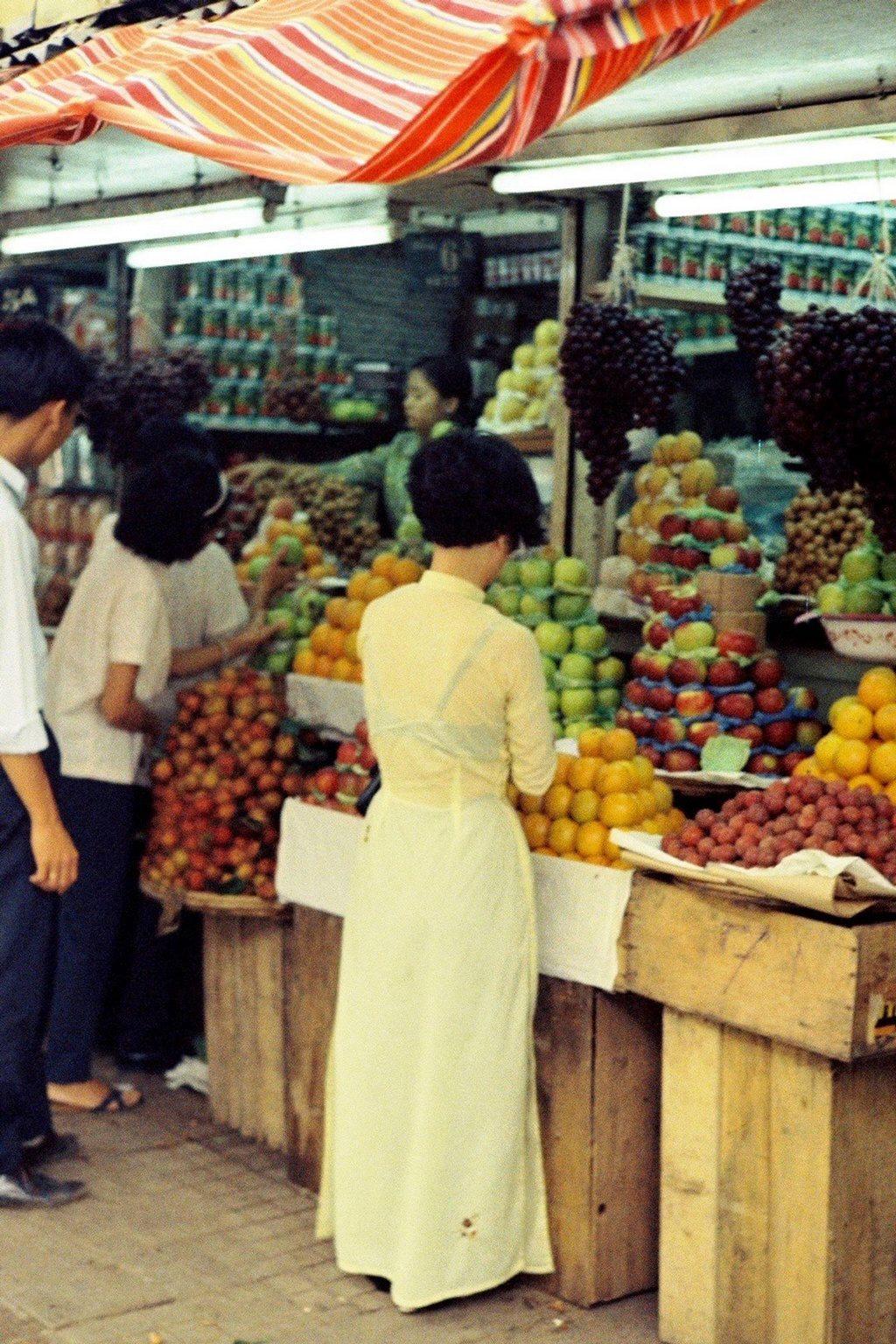 Girls in Ao Dai buying fruit_Ho Chi Minh pictures_source: buffalotrip.com