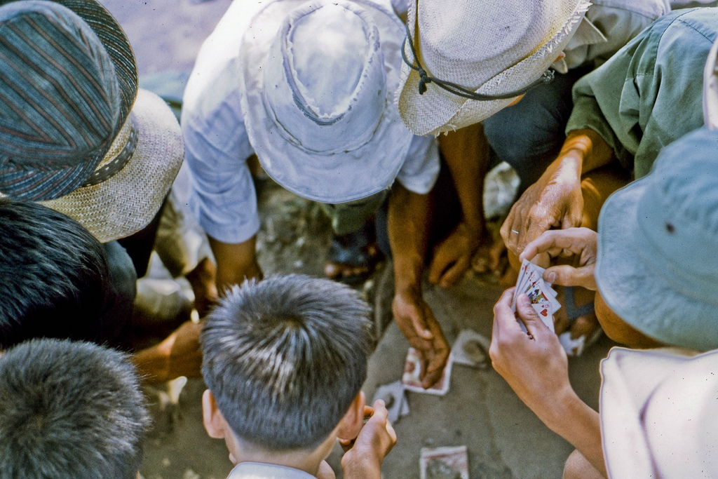 Local men take a mid-day break for a little card game. In northeast My Tho in 1969. (Dinh Tuong Province in the Mekong Delta of Vietnam) (scanned colour slide)
