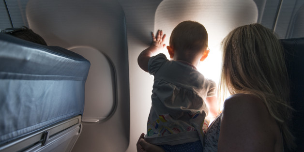Baby looking out airplane window.