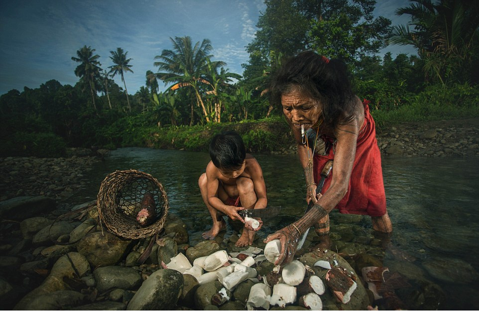 All together A young boy helps a woman to prepare what appears to be cassava or palm hearts as they stand in the river
