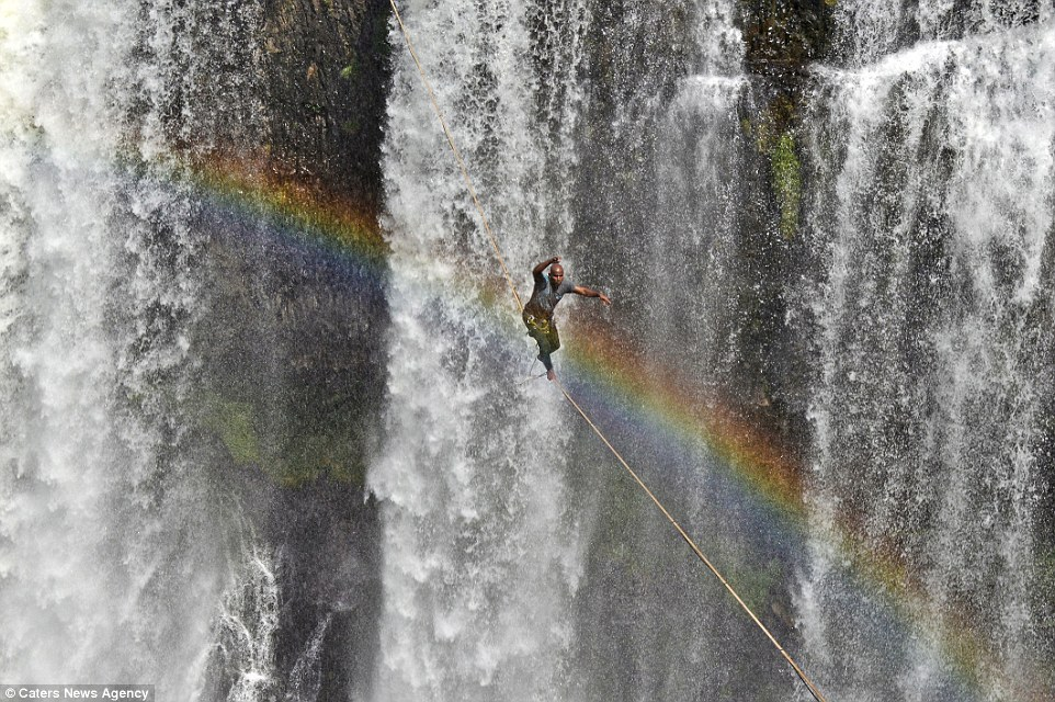 As Reginaldo weaved and balanced on the rope, a beautiful rainbow looped over and brilliantly framed the photographs. Image by Caters News Agency