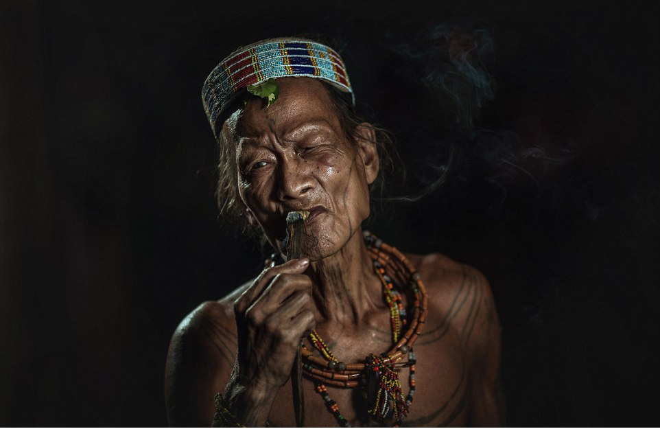 Decorated A Mentawai warrior smokes whilst wearing traditional head piece and accessories