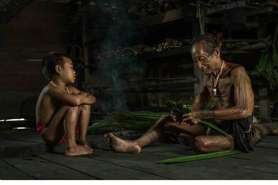 Generations An elderly Mentawai warrior shows a young boy how to fold what appears to be large palm or banana leaves