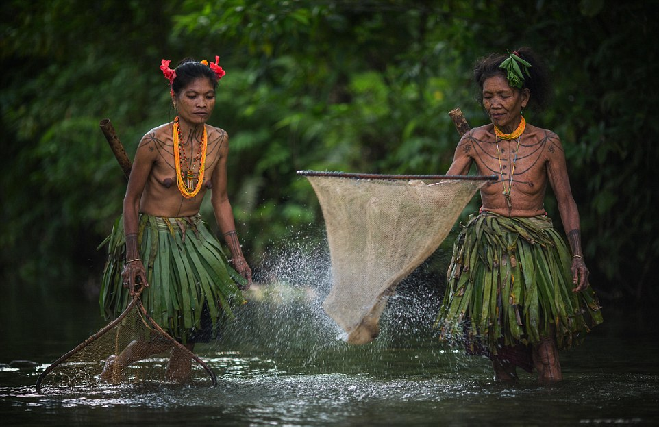 Gone fishing Two women of the tribe wear traditional skirts made from leaves as they go fishing using hand-held nets