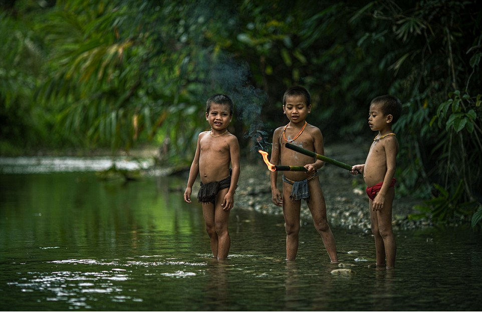 Learning by doing Three young Mentawai boys play in the local river, setting fire to bamboo sticks