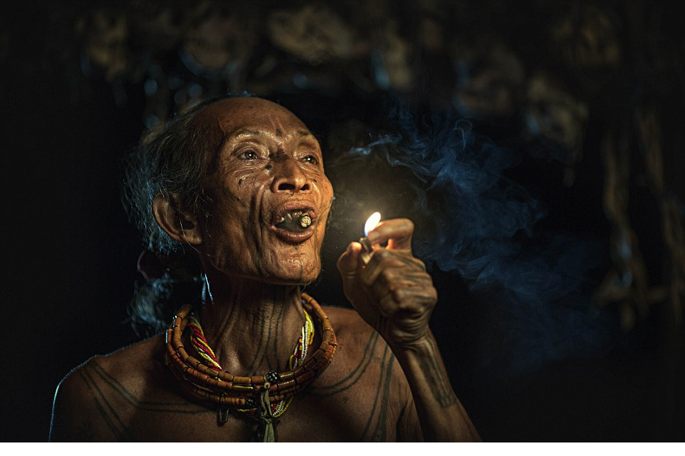 Lifelong wisdom An elderly Mentawai warrior lifts a large handrolled cigarette while sitting in his house furnished with the skulls of prey
