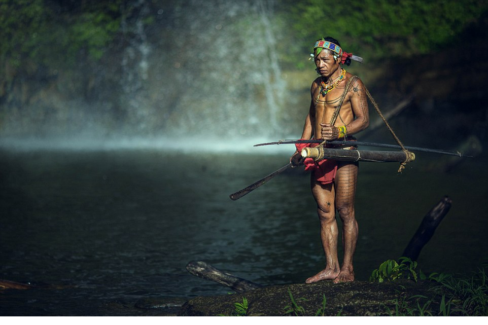 Mentawai warrior brandishes a machete knife and his hunting equipment as he prepares to go spear fishing
