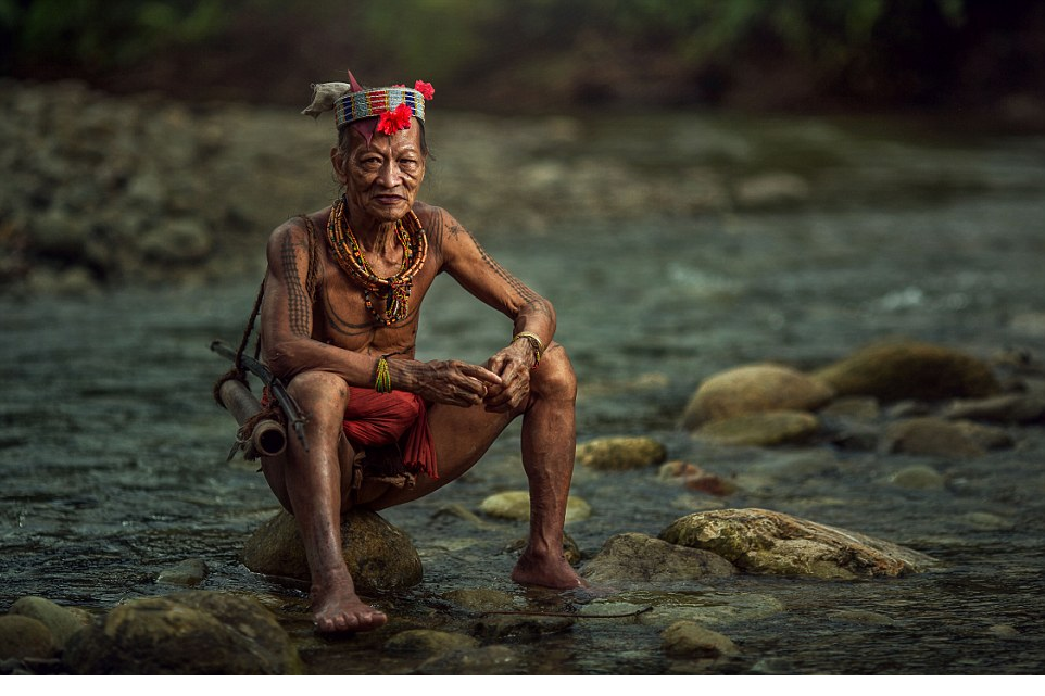 Taking a break A Mentaway warrior wearing traditional necklaces and a headband decorated with flowers sits by the river