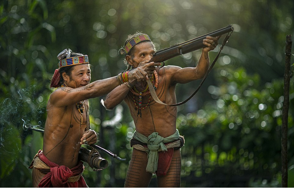 Two men of the Mentawai tribe use guns to hunt and forage for food.