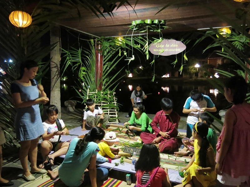 Visitors enjoy making decorations from coconut leaves Photo: dantri4.vcmedia
