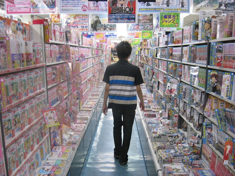 A visitor walking between the shelves of hundreds of manga (comic books in Japanese) Photo: jamonenjapon