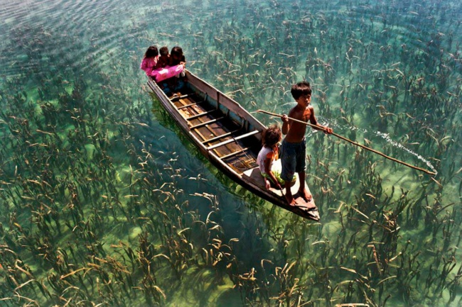 Children ride on a boat on a crystal clear lake in Sabah, Malaysia