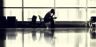 man-sitting-at-airport-hero-airport airline travel tips
