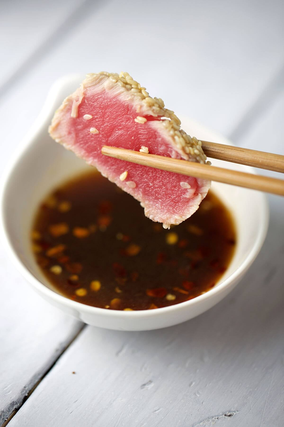 Chopsticks holding seared sesame crusted ahi tuna