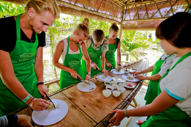 Learning how to cook Vietnamese traditionals dishes on a wooden boat-shaped table