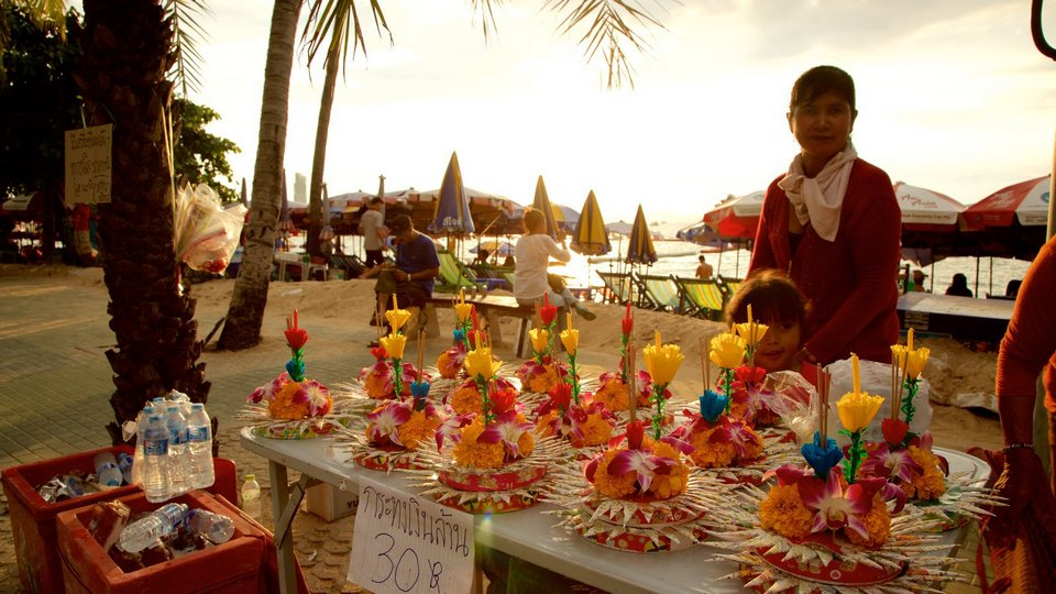 Pattaya Beach featuring shopping and a sunset as well as a small group of people