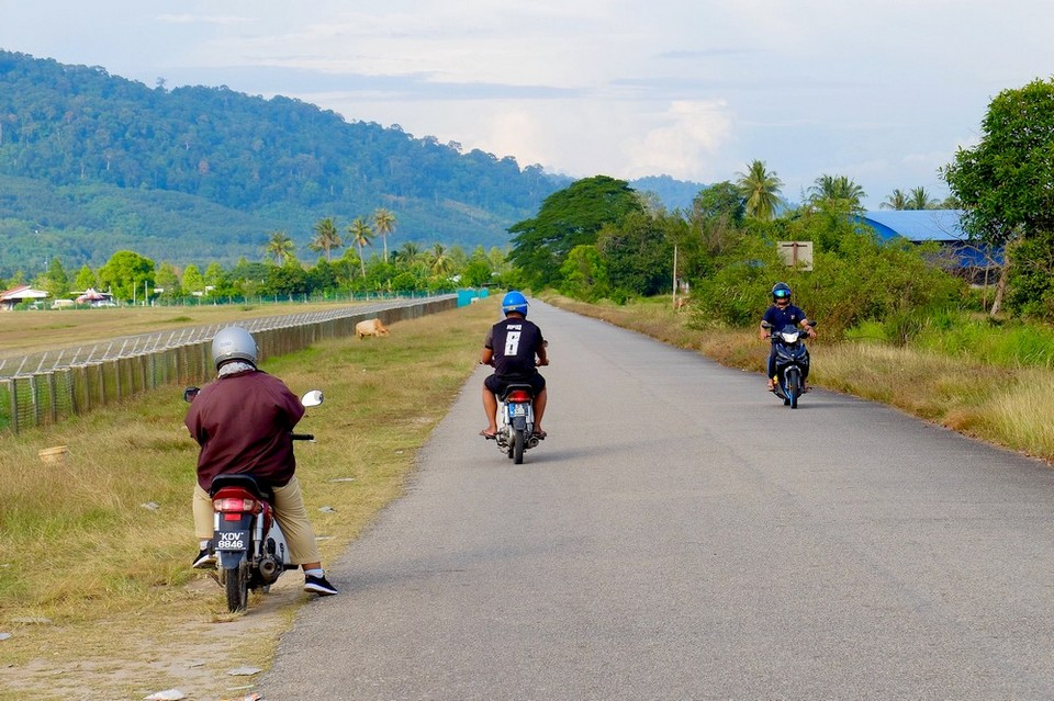 Men on scooters in Langkawi, Malaysia
