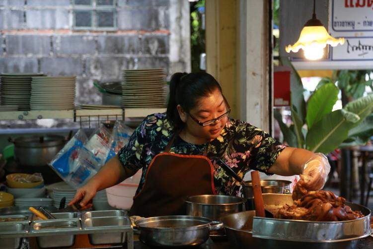 A woman is making Khao Kha Moo (stewed pork rice)