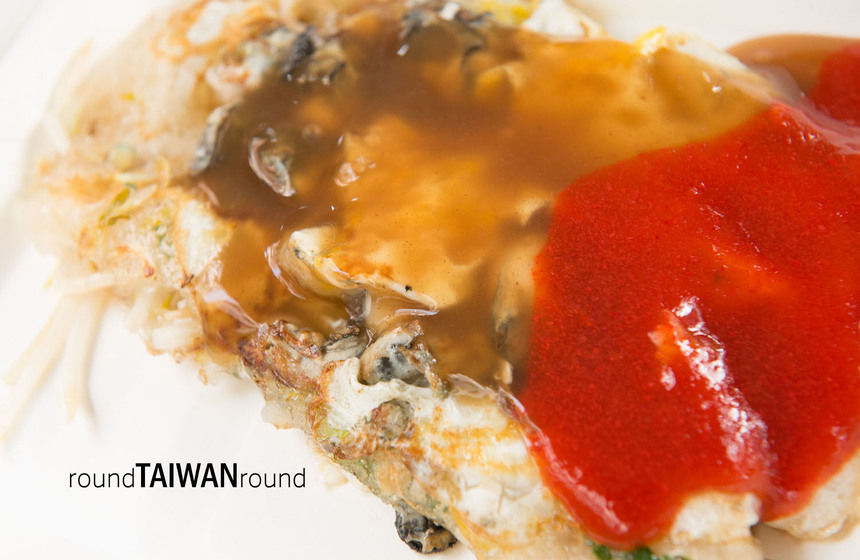Enjoying oyster omelet with chili sauce