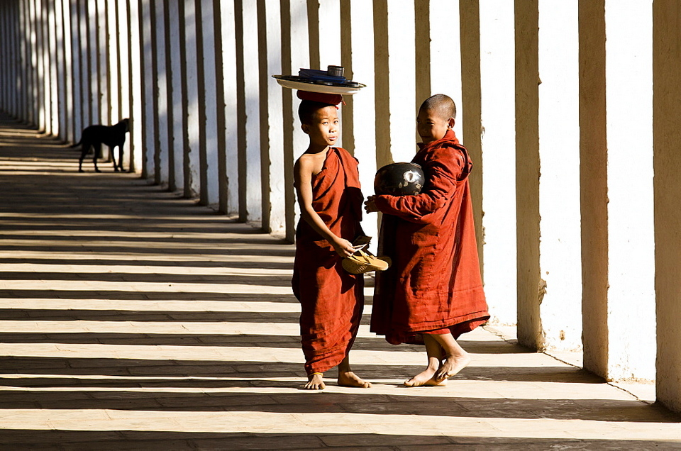 Novice Buddhist monks collecting alms, standing in the shadows of columns at Shwezigon Paya. Picture: shwezigon temple blog.