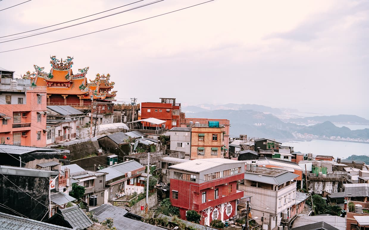 The mountainside village of Jiufen with a temple and the ocean.