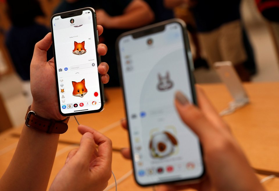 People try out the Animoji feature on iPhone X handsets during its launch at the Apple store in Singapore