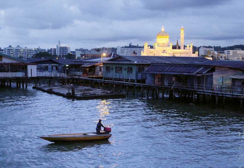 A boat passes through the Kampong Ayer water village at dusk as the Sultan Omar '