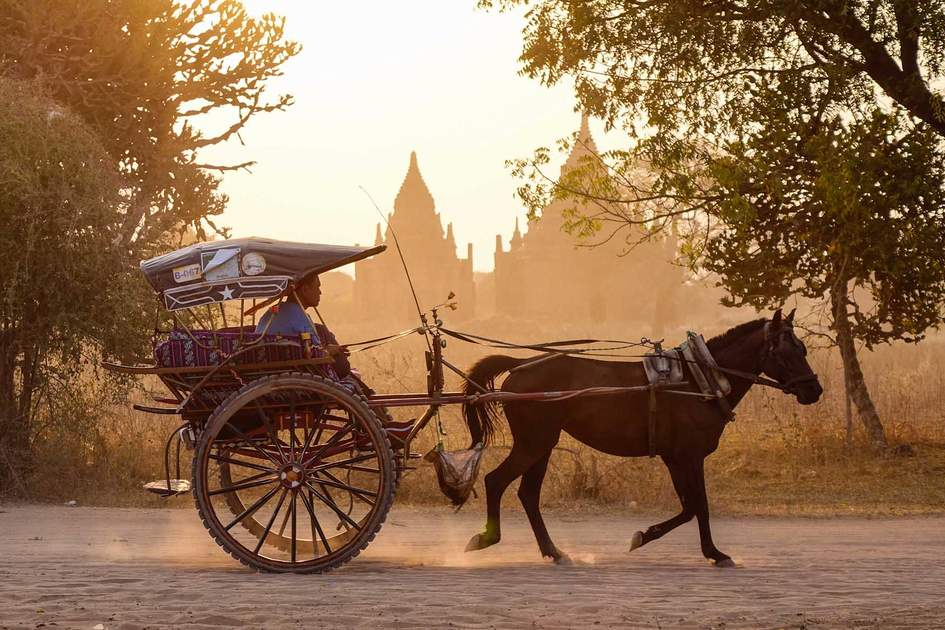 A horse cart carrying tourists on dusty road at sunset in Bagan