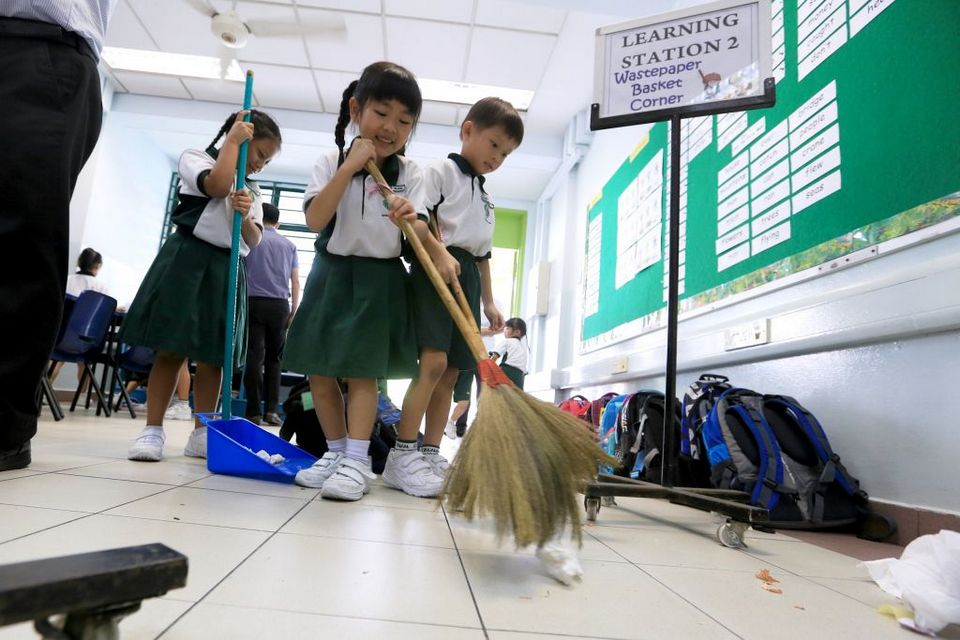 Students at Xingnan Primary School helping each other out during cleaning duties on Feb 25