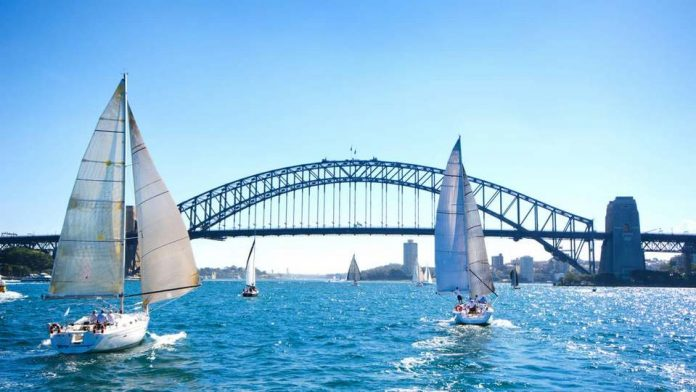 White sailboats, bridge in Sydney Harbour against clear blue sky